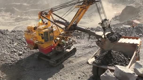 Bagger und Kipper im Steinbruch, Bagger verladen die Rohstoffe im Kipper, Arbeit im Eisenerzbruch. Bagger aus nächster Nähe.