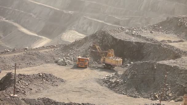 The excavator and dumper in the quarry, Large yellow excavator loaded ore into a dumper