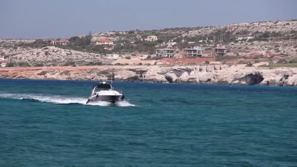 Vlny stříkající na kámen kámen na pobřeží pobřeží s luxusními jachtami v mořské zátoky a perlivá voda hladiny na pozadí