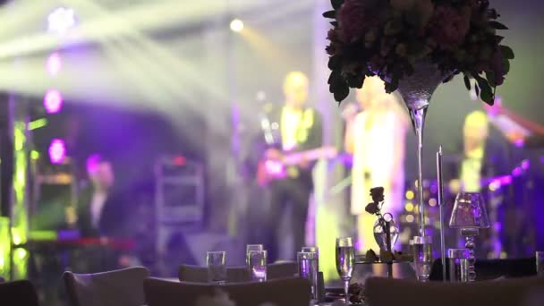 Group of silhouetted people dancing in a dark banquet hall for a wedding reception.The Wedding Banquet, people dance - shot through the wedding table decorations, wedding decoration