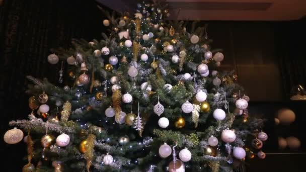 large Christmas tree in the lobby of the hotel, restaurant. Christmas tree in the hall on the background of the marble staircase with a handrail, bottom view