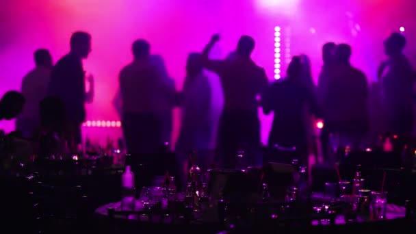 mládež party v restauraci nebo klubu, banketních stolků s alkoholu a potravin na pozadí siluety tančících lidí, scénické osvětlení a fialová výplň