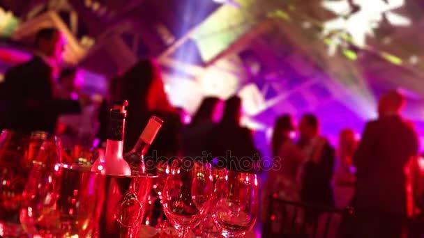 eine Jugendparty in einem Restaurant oder einer Diskothek, Banketttische mit Alkohol und Essen vor dem Hintergrund der Silhouetten tanzender Menschen, Bühnenlicht und violette Farbe