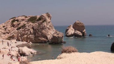 People bathe and sunbathe on a small sandy beach, the birthplace of Aphrodite on the island of Cyprus, Rocks stick out of the sea water, Beautiful beach in the Mediterranean Sea, rocky beach