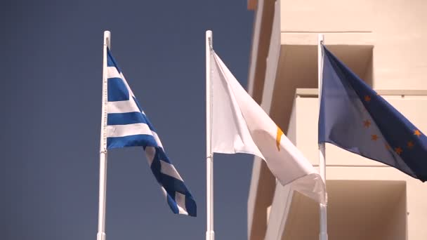 Flags of the European Union, Greece, Cyprus, the city of Aya Napa, Greece, Flags on the flagpole, the wind waving the flag, Flags on flagpole, wind waving flag, against blue sky background