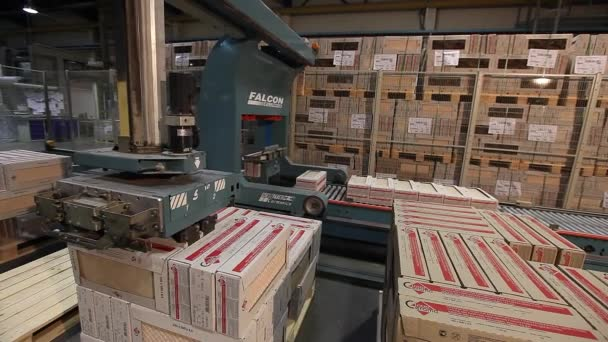 Automatic packing of products in boxes on the conveyor, close-up, packing of ceramic tiles, conveyor, modern factory, interior