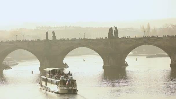 Turistů na Karlově mostě, Karlův most. Praha na pozadí turistické lodi při západu slunce