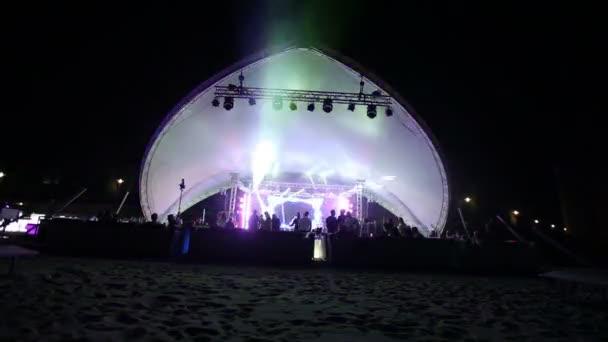 Színpadon és egy diszkó a parton. Megvilágítás este Beach Disco. koncert. Ünnepe. nyaralás. ünnepe. Táncoló emberek szórakozás a diszkóban szórakozás öröm. homokos strand