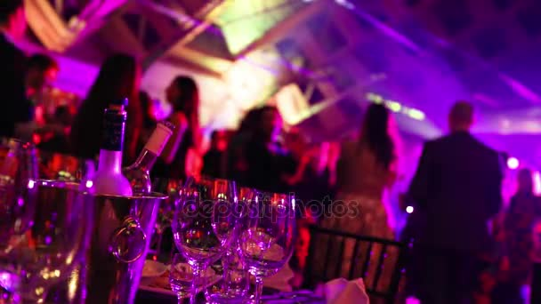 A youth party in a restaurant or a nightclub, banquet tables with alcohol and food against the background of silhouettes of dancing people, stage light and purple fill