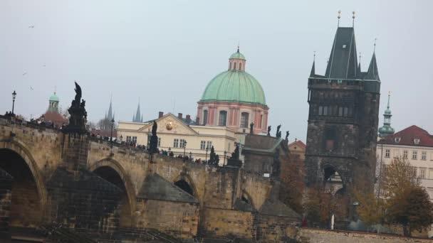 Karlův most na pozadí staré věže a zelené kopule katedrály v Praze, boční pohled, turisté projít Karlův most, Praha, 19. října 2017