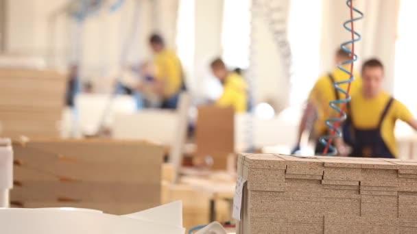 Nábytek továrních dělníků v žluté kombinézy vybírat nábytek, výroba nábytku,, průmyslové interiéru, malá hloubka ostrosti