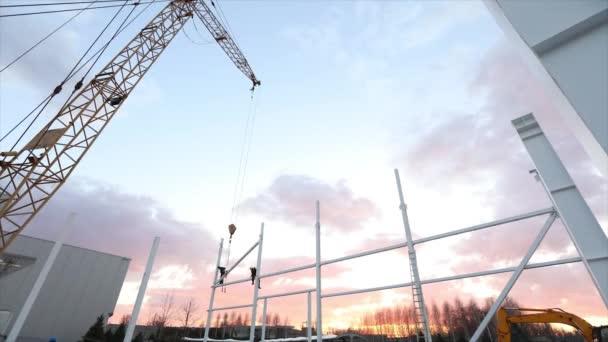 Průmyslové exteriér, Montáž kovových konstrukcí na pozadí oranžová obloha s mraky, stavební práce, výstavba průmyslová hala, timelapse