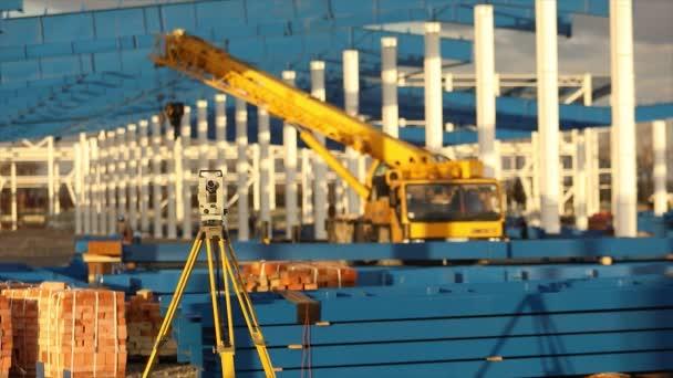Optický teodolit, stavitelé teodolit, stavební teodolit na pozadí výstavby velké průmyslové budovy nebo skladu, stavební práce