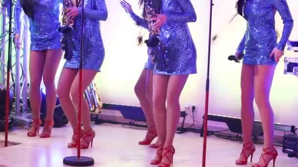 Egy női zenekar fellép, gyönyörű lányok, szaxofon, a színpadon. Lány játszik a szaxofon, a szép női láb, a női lábak vörös magas sarkú cipő