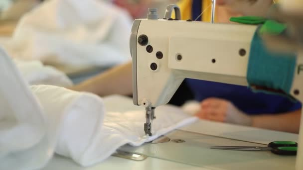 Sewing machine and white fabric, woman hand behind sewing, hand female, sewing manufacture, garment factory, woman working at a sewing machine
