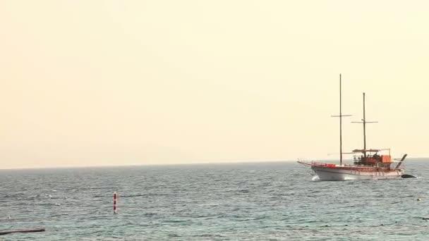 Vitorlás hajó úszik a tenger, vitorlás hajó, tenger séta-ra egy vitorlás hajó, sziluettje magányos hajó vitorlák nélkül, és az emberek a láthatáron, napos időjárás