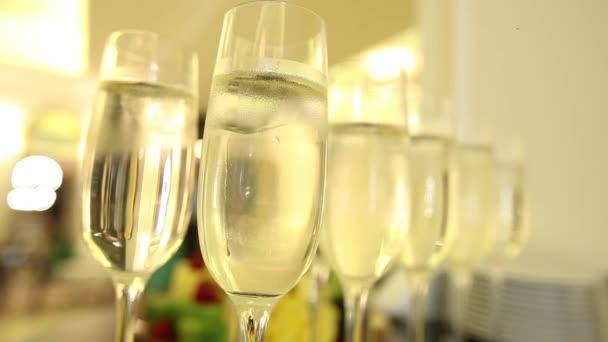 Zblízka sklenic na šampaňské s oslavou nového roku na pozadí.