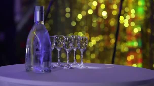 Láhev likéru na stůl, láhev vodky a sklenice na víno na bufetového stolu