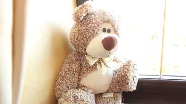 Teddy bear ül egy ablakpárkányon, aranyos maci az ablak mellett, a pillangó, a nyakán, világosbarna, a gyermek puha játék egy mackóval a pillangó, a nyakán