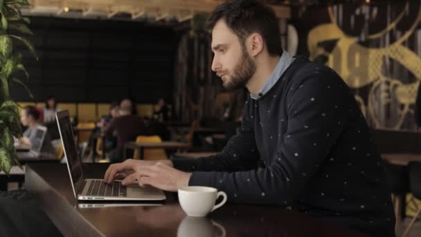 Businessman with laptop in a cafe or restaurant, Attractive male worker is using computer in cafeteria