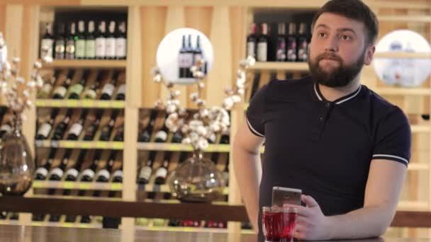 man ipster trinkt ein rotes Getränk in einem Restaurant oder Café, ein junger Mann benutzt ein Smartphone, während er einen roten Cocktail trinkt