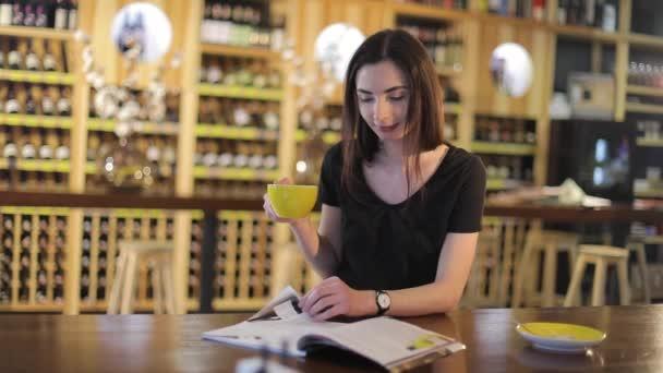 Mladá dívka pije kávu a čte módní časopis v kavárně nebo restauraci, čtení magazine žena a pití kávy, na pozadí police na víno, Vinný restaurant