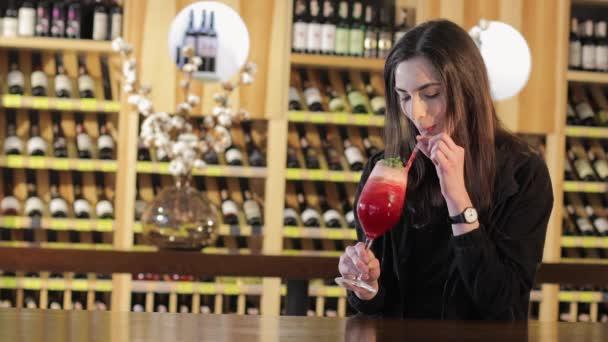 ein Mädchen trinkt einen roten Cocktail an der Bar in der Bar, eine Frau einen roten exotischen Cocktail