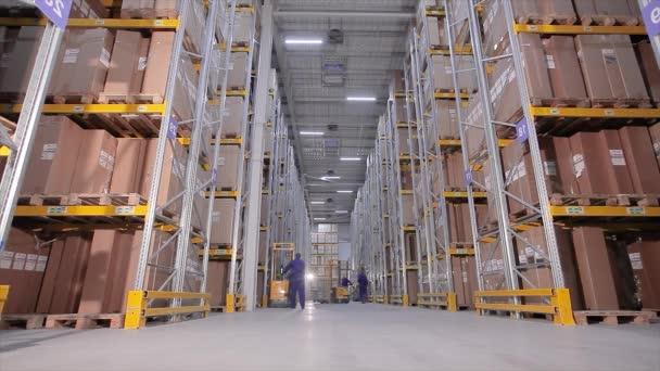 Villástargonca egy raktárban, egy férfi egy nagy raktárban elvégzi a munkát.
