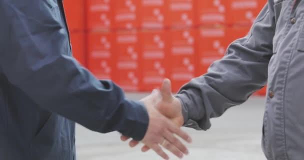 Dva muži si podají ruce. Potřesení rukou dvou mužů zblízka. Továrna si potřásá rukama, uzavírá úspěšnou dohodu