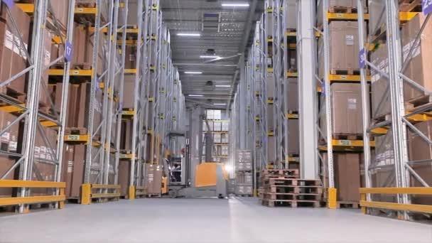 A férfiak dobozokat szállítanak egy targoncán egy raktárban, egy nagy modern raktárban. Gépek egy termelési raktárban