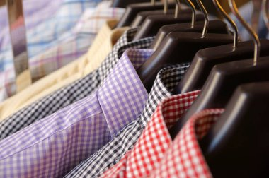 Mens plaid shirts in different colors on hangers