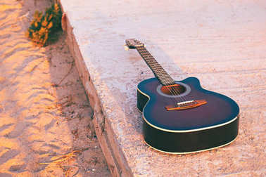 Acoustic guitar on a evening beach in sunlight toned in retro style