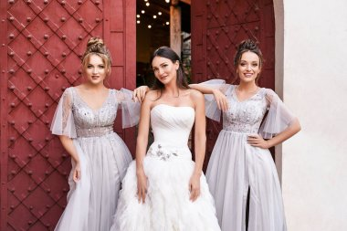 Beautiful bride and bridesmaids in gorgeous elegant stylish light grey silver floor length dresses in old beautiful European city on a wedding day.