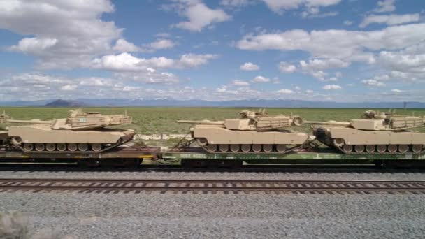 Panning view of military tanks loaded on train
