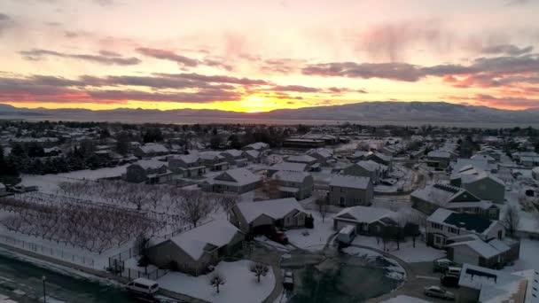 Létání nad domy pokrytými sněhem při západu slunce k obzoru nad čtvrtí.