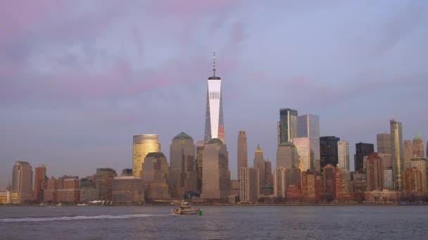 Farbenfroher Sonnenuntergang mit Blick auf die New Yorker Skyline, während ein Boot durch den Hudson River schwimmt.