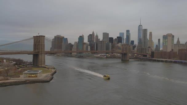 Široký pohled na New York a Brooklynský most jako plavby lodí přes East River.