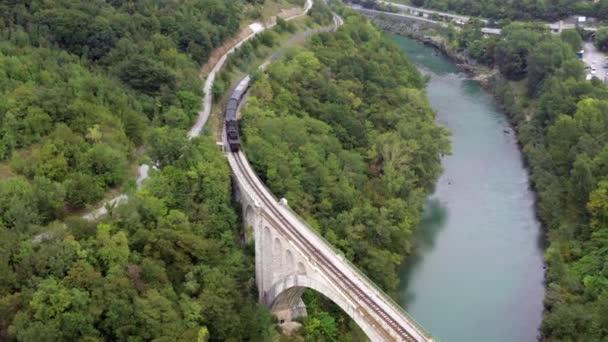 Letecký pohled na vlak přejíždějící přes řeku na mostě, jak se vine lesem.