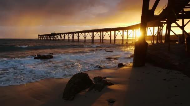 Vlny valící se na pláži během barevného západu slunce pozorovací molo táhnoucí se do oceánu na Catherine Hill Bay v Austrálii.