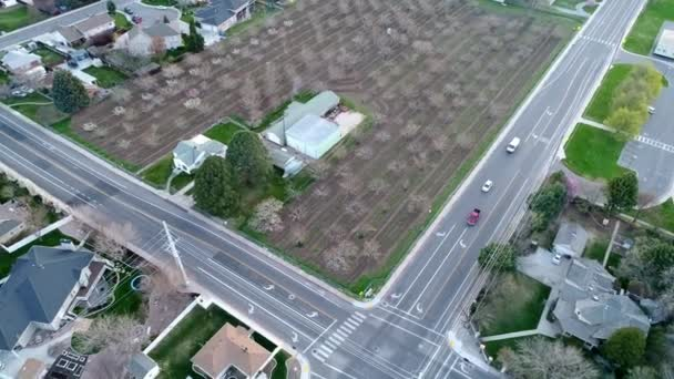 Flying over intersection as vehicles pull up to stop sign and continue to drive while flying backwards in aerial view.