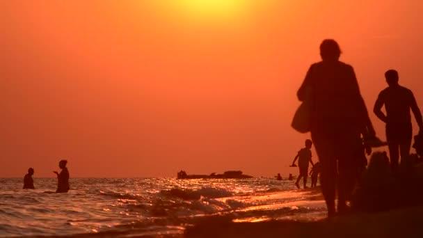 Passeggiata serale lungo la costa. Siluette al tramonto. Un gruppo di persone. A piedi sulla spiaggia sera. Una passeggiata al tramonto. Litorale di estate. Camminare sulla sabbia bagnata. Famiglia. Bambini