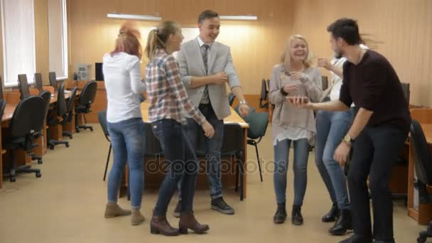 Group of young successful people dancing in a computer room