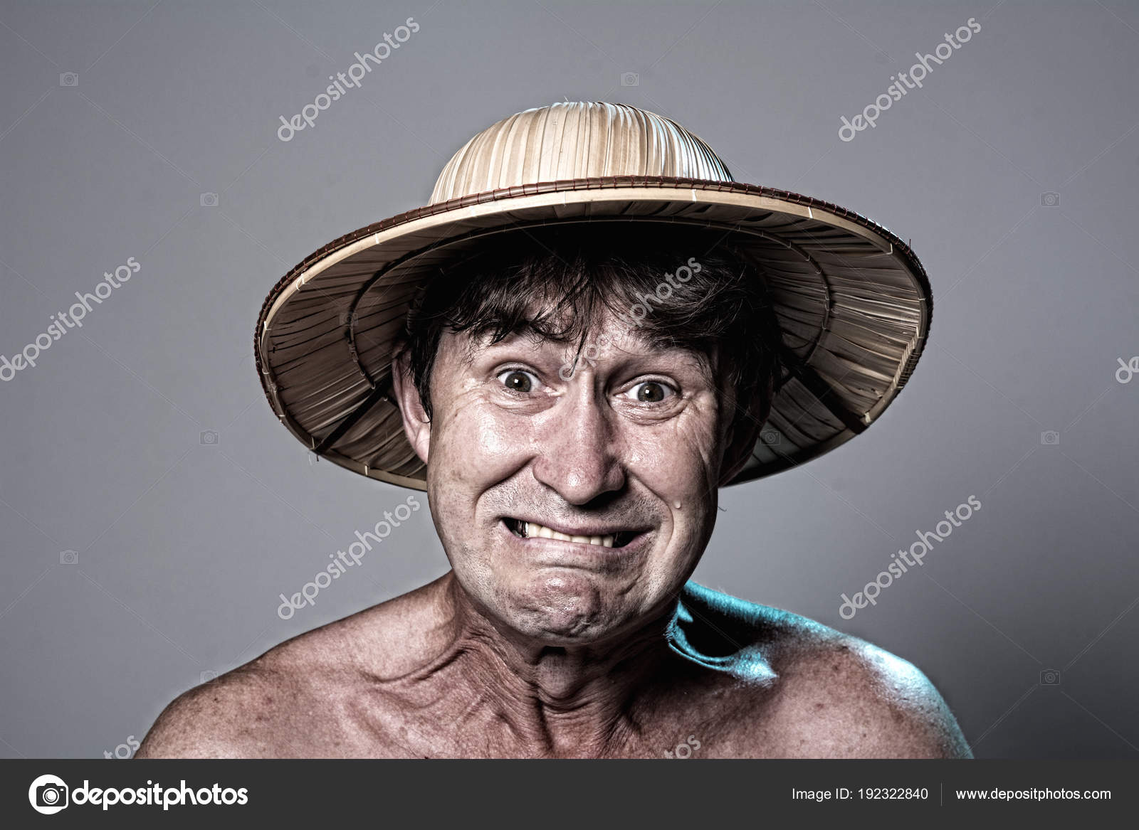 Ritratto del primo piano di un uomo amareggiato con un torso nudo in un  cappello su uno sfondo grigio. Un uomo in un cappello di paglia Mostra i  denti ... 9e0e6a7fcacd