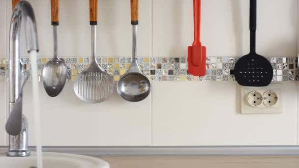 Tap versando acqua utensili cucina appendere sullo sfondo