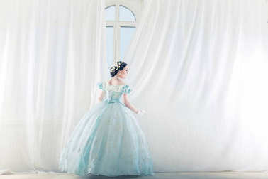 Elegant woman at a high window in historic dress, straightens the curtains, and waiting for friends to prom to dance