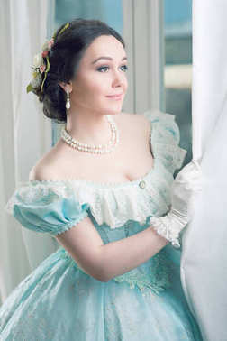 Elegant woman in historical dress and in jewelry waiting for friends at the ball to dance