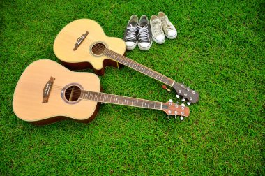 Two guitars and two pairs of shoes on bright green grass
