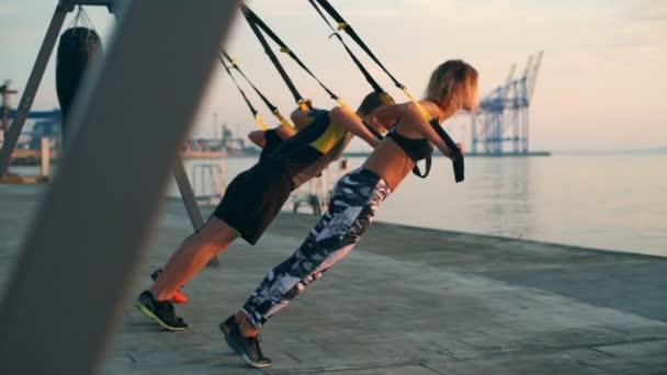 Krásné sportovní lidé výcvik zbraně s trx v moři sunrise. Zpomalený pohyb