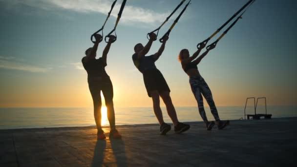 Siluety sportive lidí školení s trx na moři východ slunce. Zpomalený pohyb
