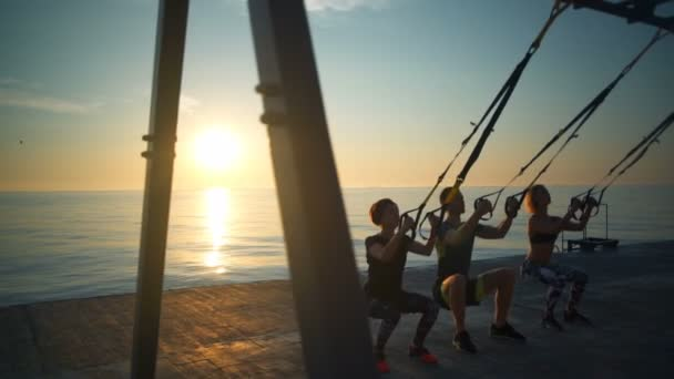 Silhouettes of sportive people training squats with trx at sunrise. Slow motion.